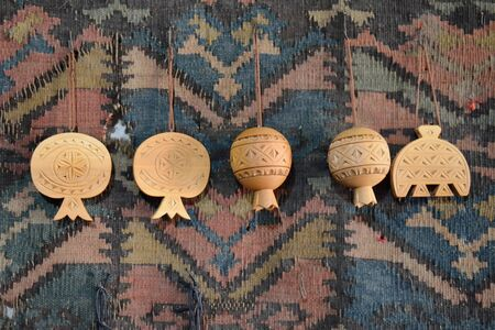 Carved wooden pomegranates on a traditional Armenian carpet Stock Photo