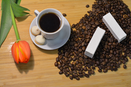 mocca: cup of hot mocca coffee with vanilla pastille on coffee beans and a fresh flower