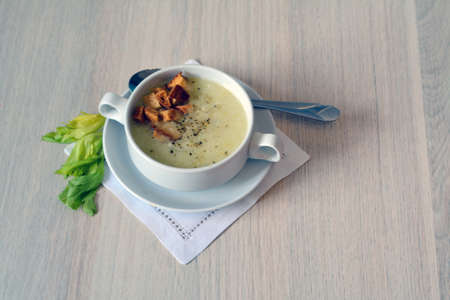 celery soup in a bowl with croutons in it