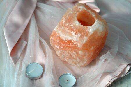 salt lamp: orange salt lamp and candles on pink cloth