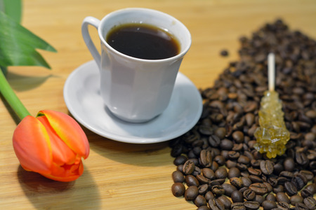 coffee, coffee beans, fresh flower and sugar stick on coffee beans