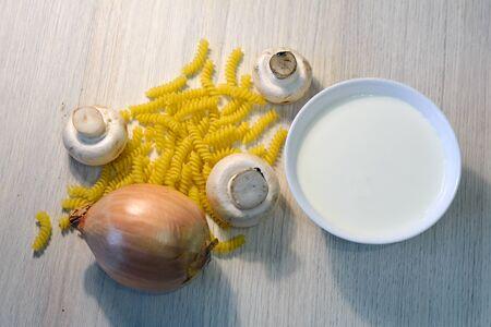 fusilli: fusilli with raw mushrooms, onions and cream on the table Stock Photo