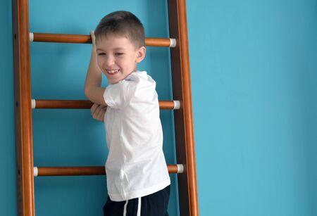 upward struggle: smiling kid stands on the ladder