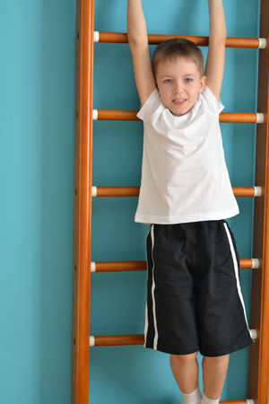 upward struggle: boy hangs off the ladder ready to jump Stock Photo