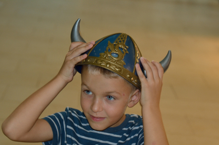 boy in the viking helmet smiling and looking aside