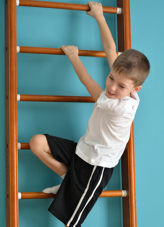 upward struggle: smiling boy looking down from the ladder