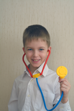stethoscope boy: boy plays a doctor with a stethoscope in his hand