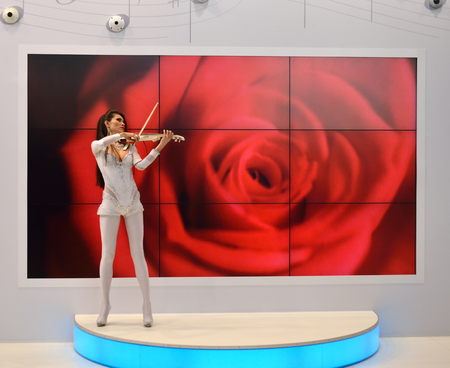 rose photo: young girl  and the violin on the exhibition center playing in front of the screen with a rose. Photo taken 13 April, 2015