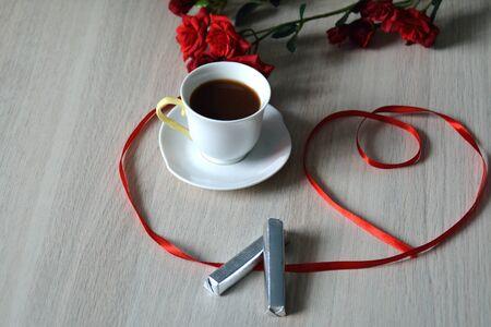 cafe bombon: taza de café con dos palos de chocolate en la mesa