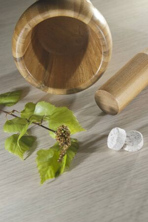 pounder: wooden pounder tool, fresh leaves and tablets on the table Stock Photo
