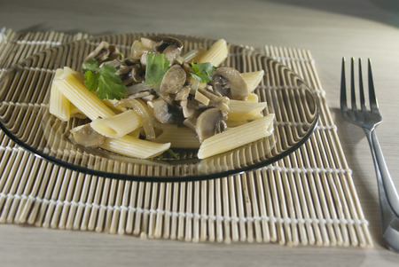 flavorsome: Portion of penne rigato with mushrooms on the plate Stock Photo
