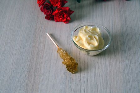 exfoliate: natural sugar scrub in a bowl with a sugar stick