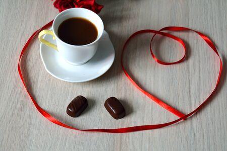 cafe bombon: caf�, dulces y un coraz�n cinta sobre la mesa Foto de archivo