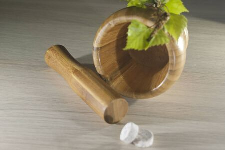 pounder: wooden pounder with fresh leaves and tablets on the table Stock Photo