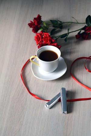 cafe bombon: taza de caf�, chocolates y flores en la mesa