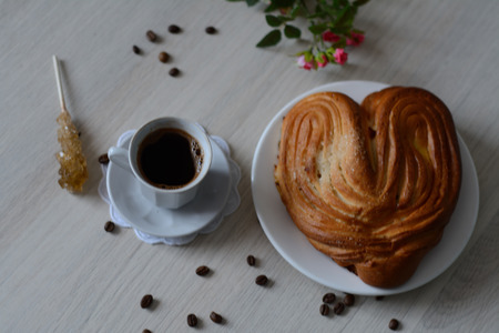 scattered in heart shaped: coffee and a fresh bun on the table Stock Photo