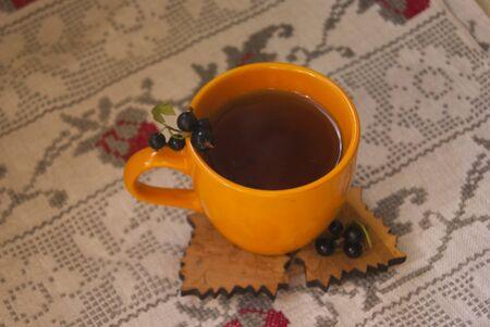 black currants: Clay cup of tea with black currants
