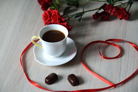 cafe bombon: cup of black coffee with two oval bonbons, flowers and a ribbon