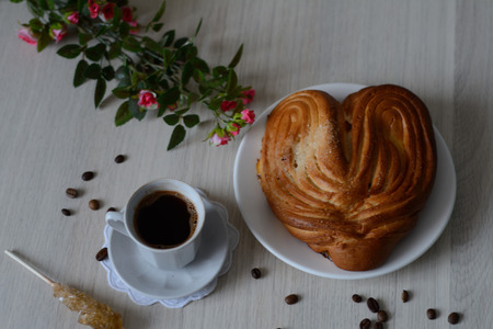 scattered in heart shaped: heart-shaped bun on saucer and coffee