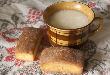 sour milk: clay cup of sour milk with two sweet biscuits, on a towel