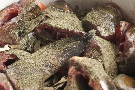 tench: raw tench with dry herbs in a pan