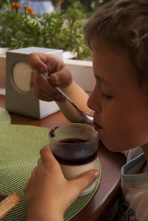 kafe: Cute boy eating dessert with a spoon