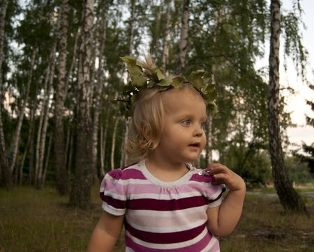 Toddler girl looks in the far with a wreath Banco de Imagens