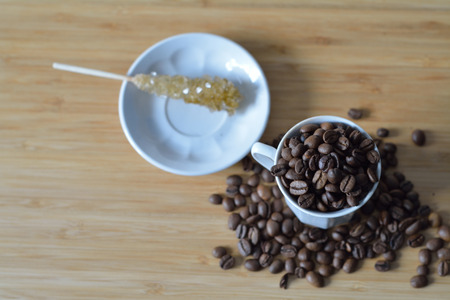 candy stick: coffee beans in a cup, candy stick on a saucer