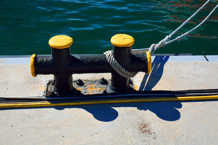 cabling: metal bitt on a pier with a mooring line and a cabling in front next to the sea
