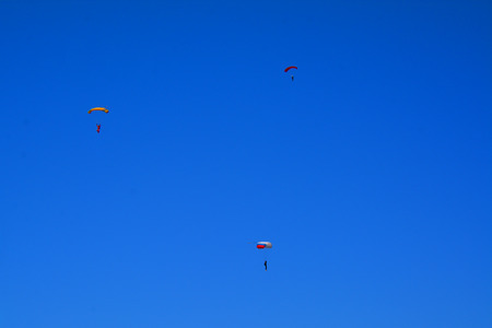 parachutists: Three small parachutists in the sky