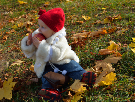 manteau de fourrure: toddler in white fur coat  sitting in the autumn leaves and eating an apple