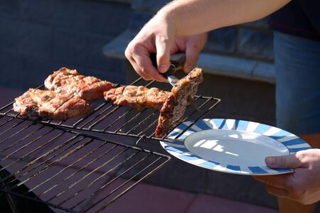 hands off: mans hands with a plate and a knife taking the meat off the grill