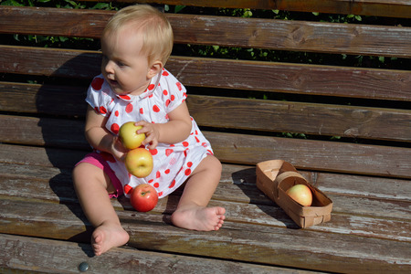 looking aside: The baby girl holding apples and looking aside