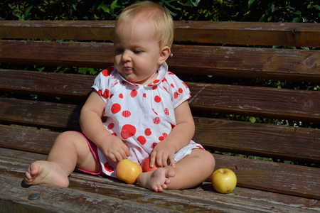 looking aside: A cute infant girl looking aside with apples in her hands