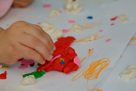 playdoh: Child playing with colored red plasticine on the table Stock Photo