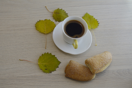 quaking aspen: Cup of coffee on the table with yellow aspen leaves Stock Photo
