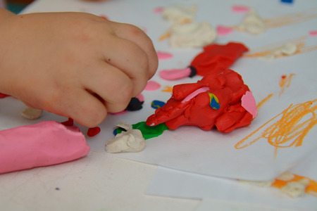 playdoh: Childs hand on the table moulding with color plasticine Stock Photo