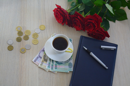 dram: Several Armenian dram notes with roses and a cup of cofee and a pen, business concept