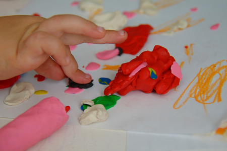 playdoh: Toddlers palm pressing the plasticine with the finger on the table Stock Photo