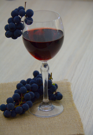 Glass of young red wine with a bundle of grapes, on the sackcloth