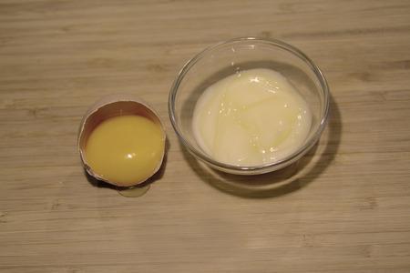 cremas faciales: Amarillo crema facial y una yema de huevo, sobre la mesa Foto de archivo
