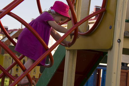 small girl in the pink dress in the iron ladder