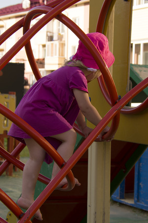 small blonde girl climbing on the iron ladder in summer