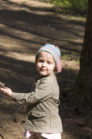 toddler girl in the forest having the sticks in hands Stock Photo