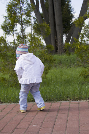 toddler girl in a hat watching the grass, from the back Stock Photo