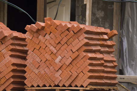 angled: angled pile of the red bricks, on the site Stock Photo