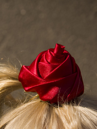 childs ponytail with a red rose
