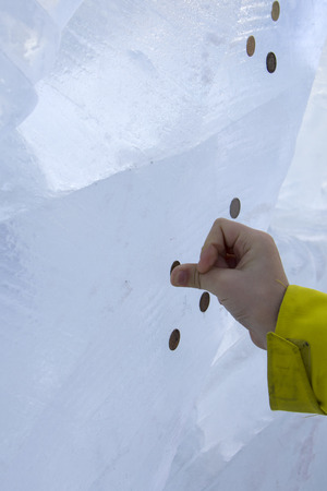 boy imprinting the coin into the ice Stock Photo