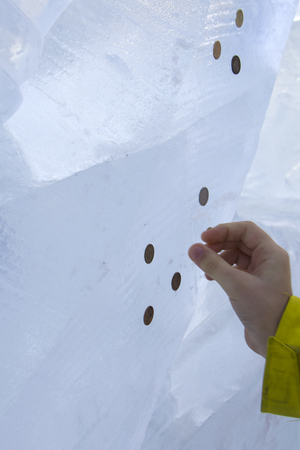 hand of the boy imprinting the coins into the ice