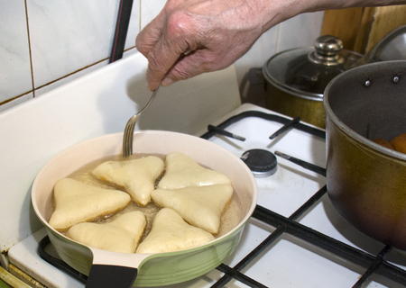 triangle pies in hot oil, on the frying pan Stock Photo